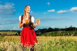 donna con tracht, birra e pretzel in Baviera foto