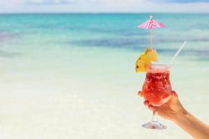 cocktail della holding della donna sulla spiaggia tropicale foto