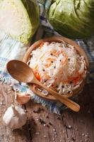 crauti e carote in una vista superiore verticale del piatto di legno foto