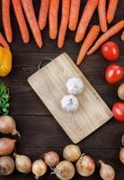 aglio sul tagliere con mix di verdure sul tavolo foto