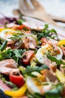 insalata con salmone e verdure nel piatto rosa sul giornale foto