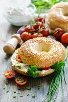 bagel con crema di formaggio, pomodori ed erba cipollina per uno spuntino sano foto