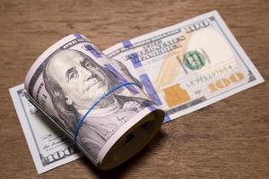 rotolo di banconote da cento dollari foto