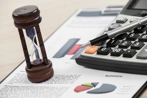 grafici e diagrammi finanziari con clessidra foto