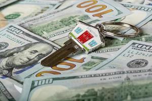 chiave di casa e banconote da cento dollari foto