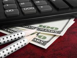 concetto di affari - calcolatore, dollari e penna, fine in su foto