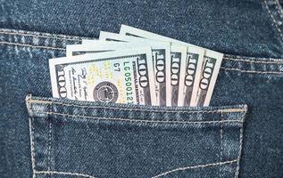 banconote di dollari americani nella tasca posteriore dei jeans foto