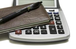 Chiuda in su del calcolatore con il libretto degli assegni e la penna foto