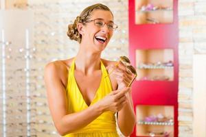 giovane donna all'ottico con gli occhiali foto