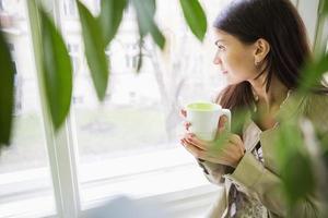 giovane imprenditrice con una tazza di caffè guardando attraverso la finestra in ufficio foto