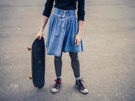 giovane donna in piedi nel parco con uno skateboard foto