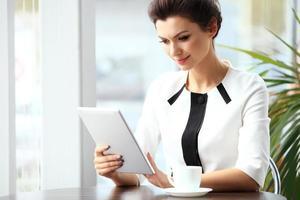 donna di affari pensierosa che legge un articolo sul computer tablet foto