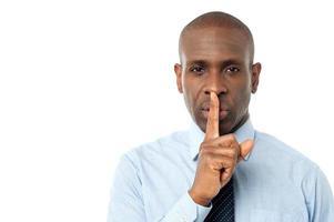 l'uomo d'affari mostra il gesto di silenzio foto
