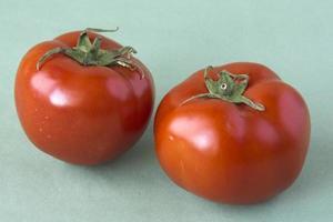 due pomodori su uno sfondo verde foto