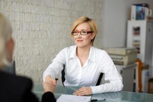 stretta di mano della donna di affari con il cliente foto