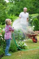 padre e figlia innaffiare le piante in giardino
