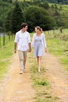 coppia tenendosi per mano camminando in campagna foto