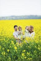 famiglia con ragazze gemelle in piedi nel campo di colza foto