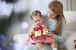 madre e figlia che aprono la scatola del regalo foto