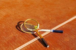 vecchia racchetta da tennis sul campo di sabbia foto