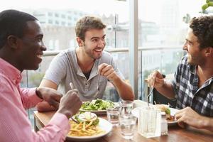 tre amici maschi che godono del pranzo al ristorante sul tetto foto