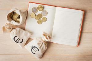 sacchi di denaro con monete in euro e taccuino aperto foto