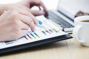 uomo d'affari che analizza i grafici di investimento con il computer portatile foto