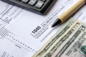 moduli fiscali 1040 con gli occhiali, i soldi e la penna foto