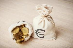monete in euro in sacchi di denaro su fondo in legno foto