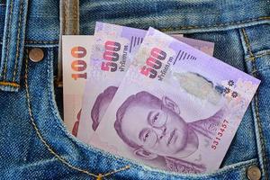 500 e 100 banconote nella tasca dei jeans blu da uomo foto