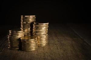 pile di monete d'oro su uno sfondo scuro naturale