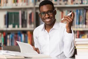 giovane studente seduto in biblioteca foto