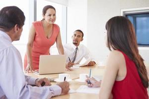 quattro persone di affari che hanno riunione nella sala del consiglio foto