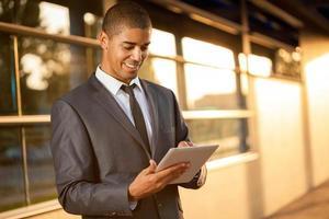 uomo d'affari afroamericano che per mezzo della compressa digitale
