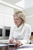 donna che calcola le fatture domestiche con il calcolatore in cucina foto