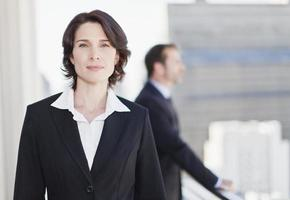 imprenditrice sorridente in piedi in ufficio foto