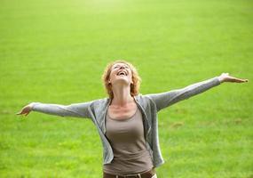 donna più anziana spensierata che sorride con le braccia aperte foto