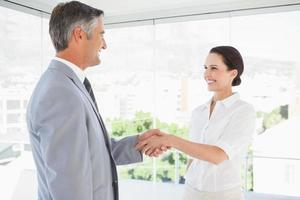 sorridenti uomini d'affari si stringono la mano foto