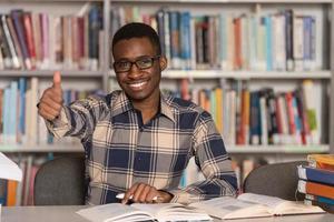 uomo africano in una biblioteca che mostra i pollici in su foto