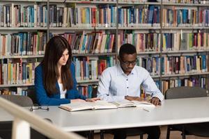 studente maschio che dorme in biblioteca foto