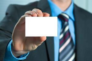 uomo d'affari che passa un biglietto da visita in bianco foto
