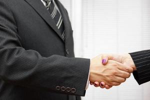 stretta di mano di soci d'affari, uomo e donna in ufficio foto