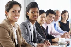 linea di uomini d'affari che ascolta la presentazione seduti a glas foto