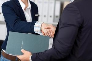 uomini d'affari della stretta di mano in ufficio foto