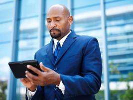 uomo d'affari afroamericano facendo uso della compressa foto