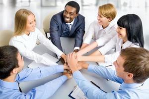 squadra di affari che fa mucchio delle mani sul posto di lavoro foto