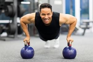 uomo che fa esercizio pushup con campana bollitore foto