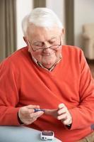 uomo anziano facendo analisi del sangue di glucosio a casa sua foto