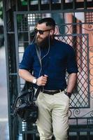uomo barbuto in piedi e ascoltando musica