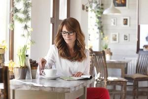 bella donna seduta alla scrivania nella caffetteria foto